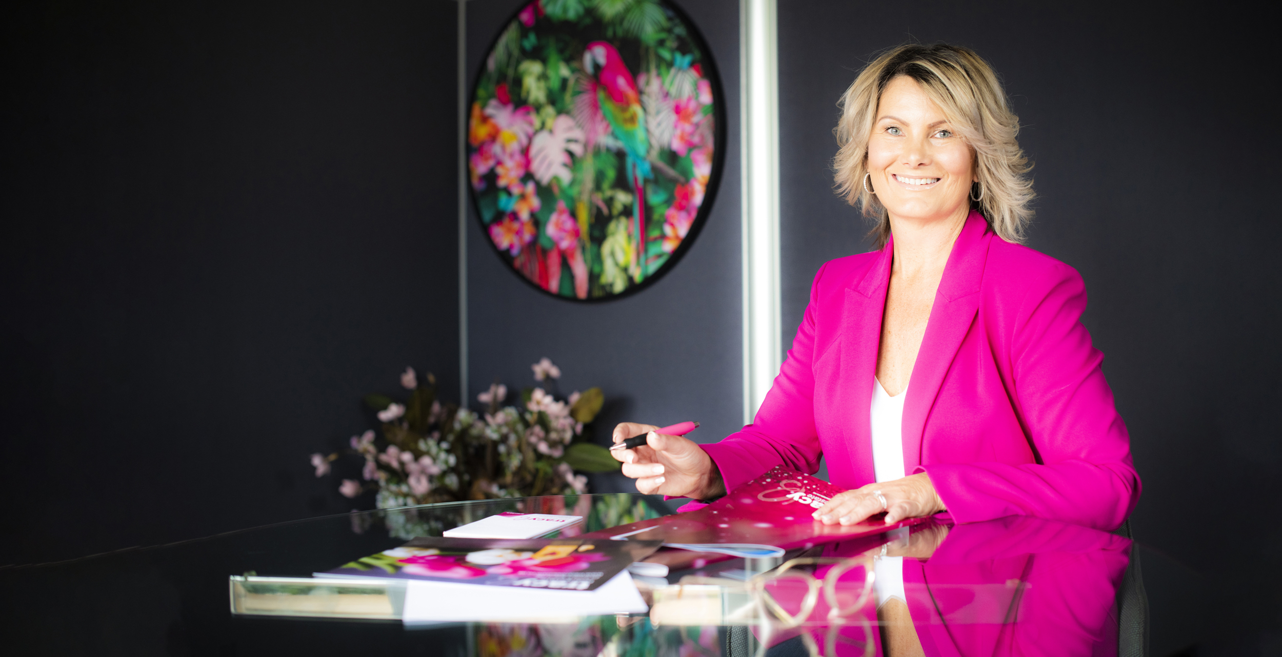 Real Estate Agent, Tracy is sitting at her desk smiling and wearing a striking, magenta blazer.